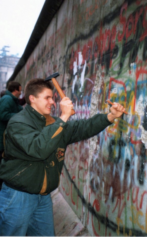 Een man vernield de Berlijnse muur
